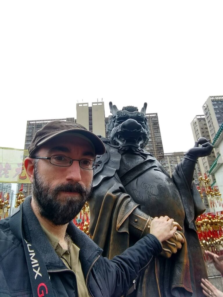 Me holding the hand of a dragon statue.