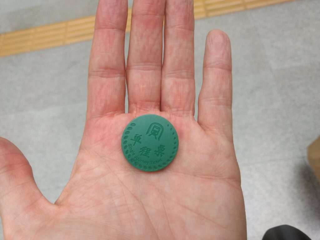 Single Journey Ticket. Green round token made of plastic.
