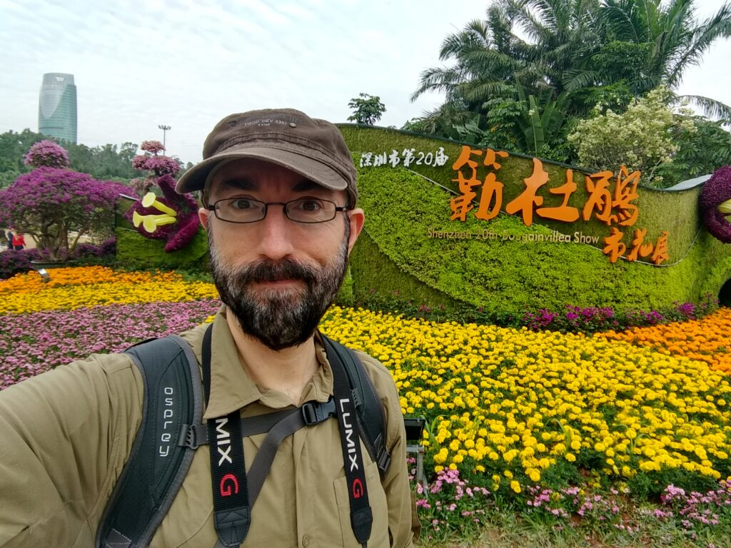 Me in front of a big ornament make of flowers of different kind and color.