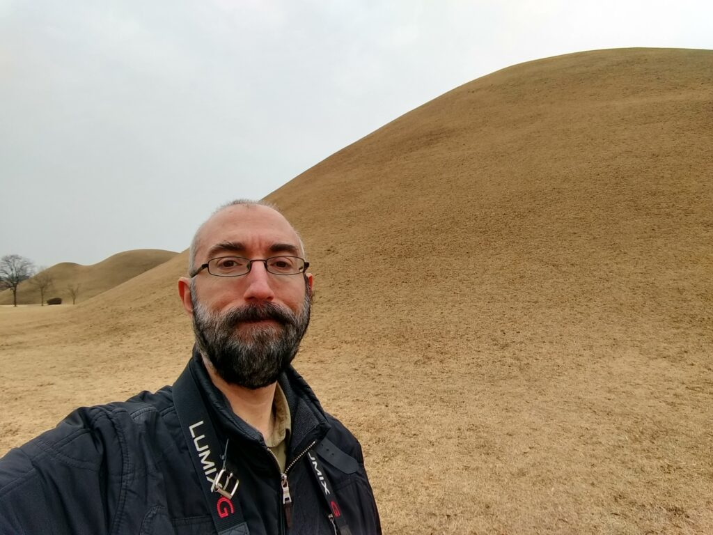 Me with a tumulus in the background. The grass is yellow.