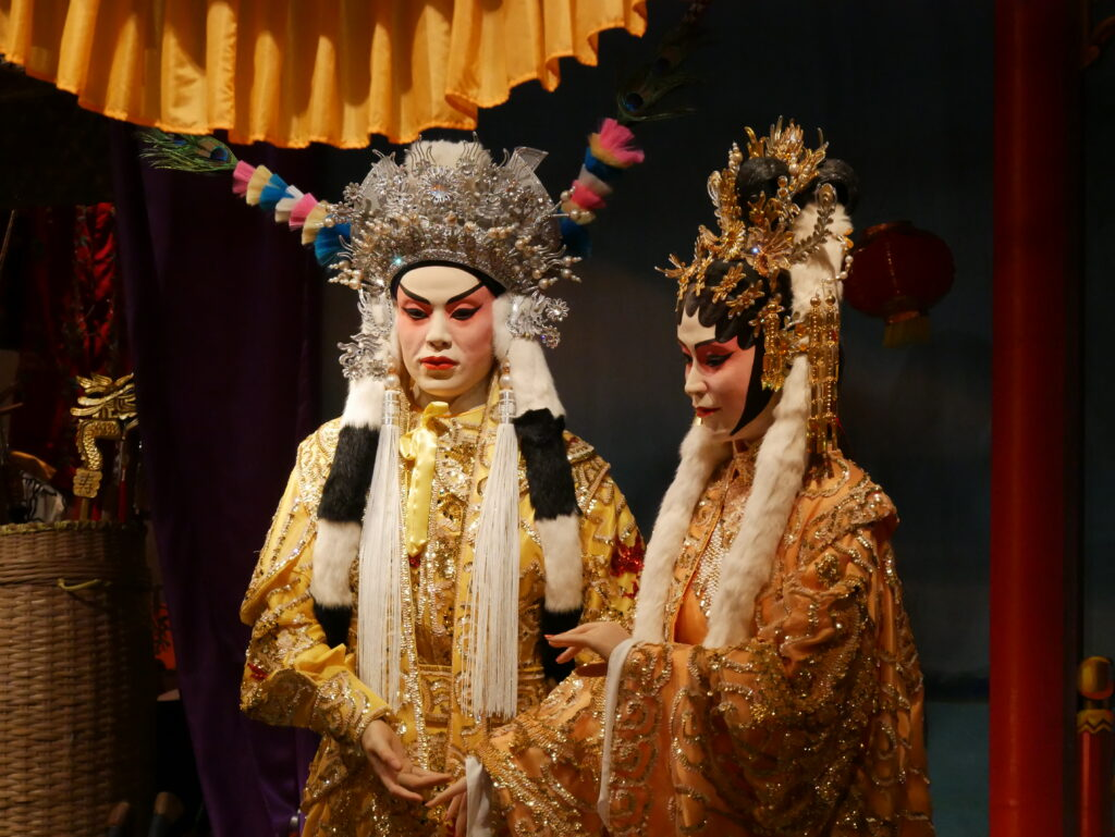 Two figures dressed in colorful traditional clothes for the theater.