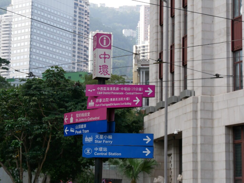 A poster with signs written in English and Chinese. The three pink signs point to touristic spots like St. John's Church. The three blue signs point to transport stations like Central Station.
