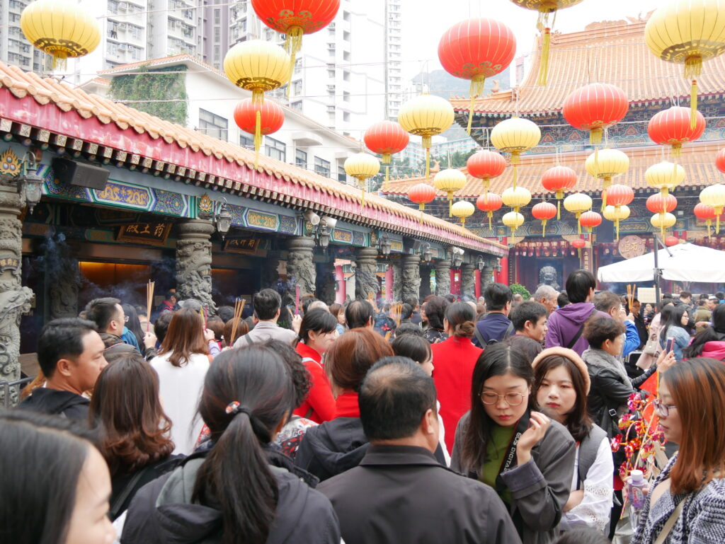 A crowd of people in a temple. There are colorful lanterns and some smoke from burning incense.