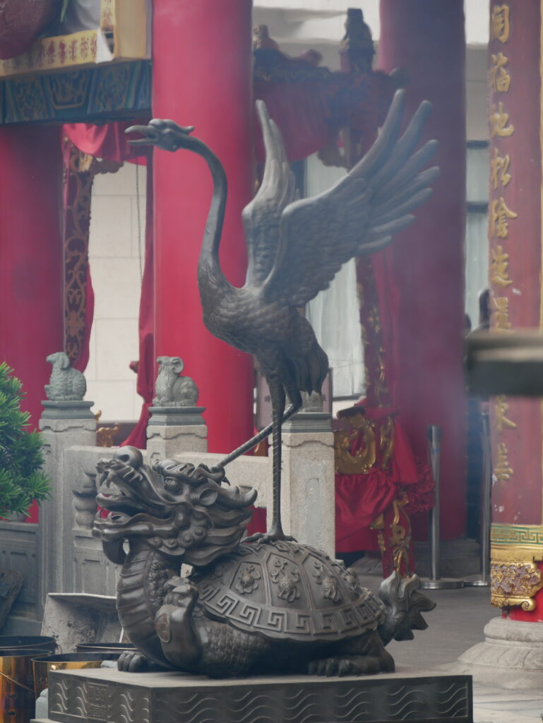 Statue of a bird and a turtle. There is some smoke from burning incense.