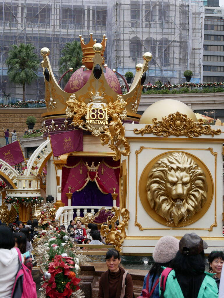 Throne and crown painted in gold. People around are taking selfies with their phones.