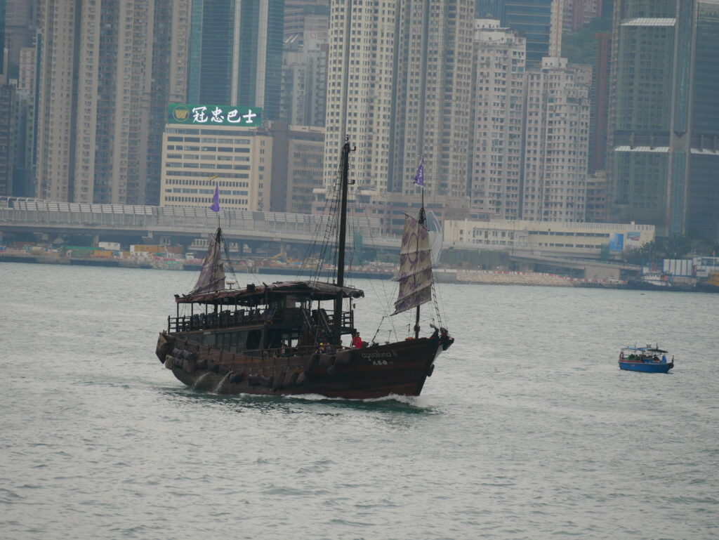 An old style ship in the sea. In the background can be seen the tall buildings from Hong Kong island.