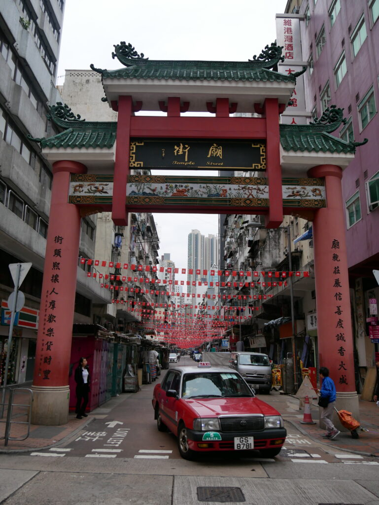 The gate to enter Temple Street. A taxi is passing by. The gate is red and its roof is of green tiles.