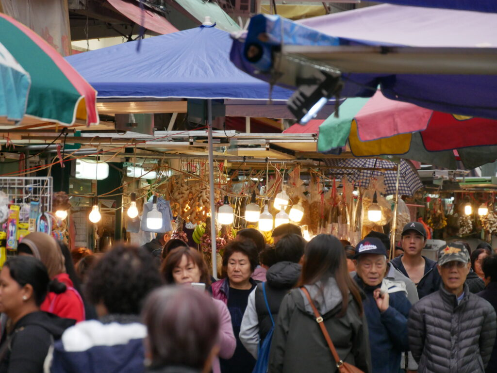 People at the market. One shop can be seen selling food.