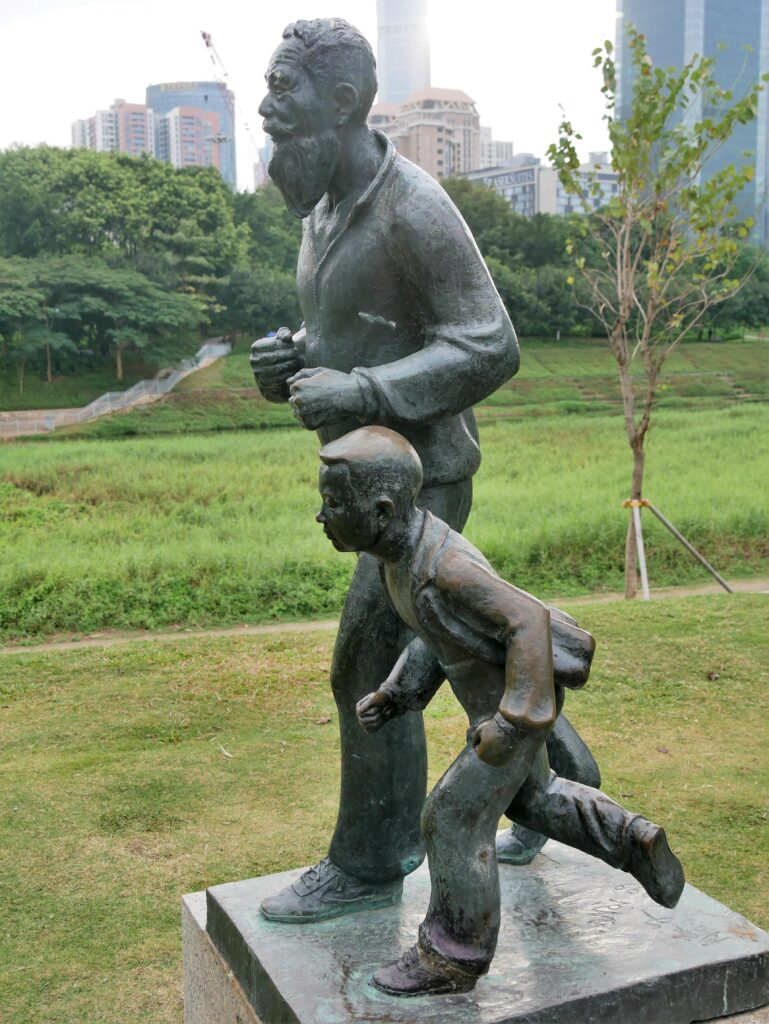 A bronze statue of an old mine jogging with a small child. In the background there are green grass and trees.