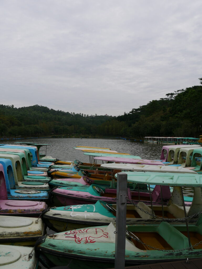 Colorful recreational boats in the lake. A forest can be seen in the background.