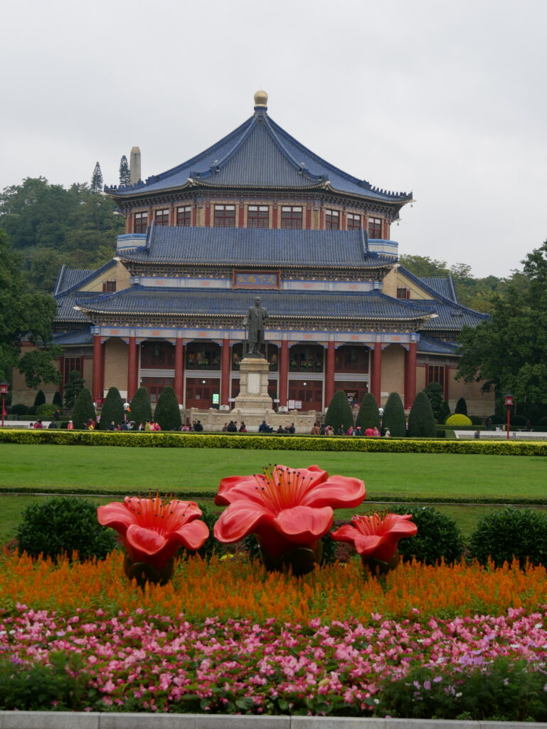 Big building with a traditional Chinese style roof. In the front there is a statue of a man with a cane.