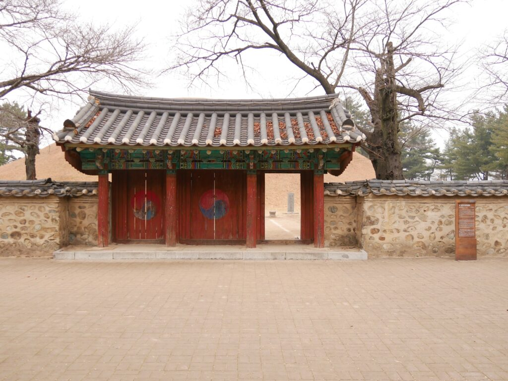 A gate with three doors. Two are closed and have the Korean symbol on it.