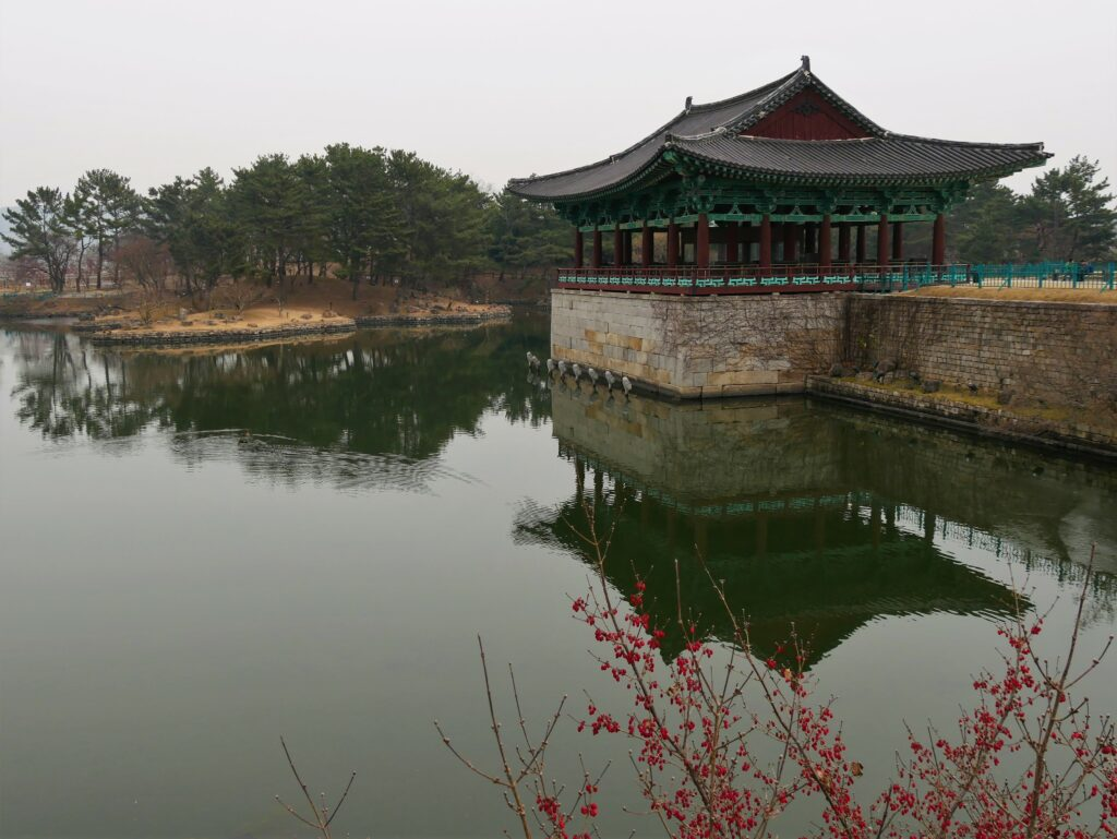 A traditional Korean building reflects in the water of the pond.