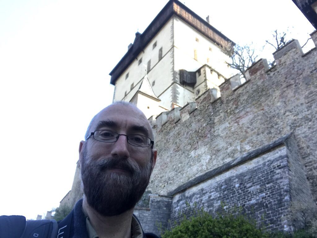 Josep Panadero in front of Karlštejn with part of a wall and a tower in the background.